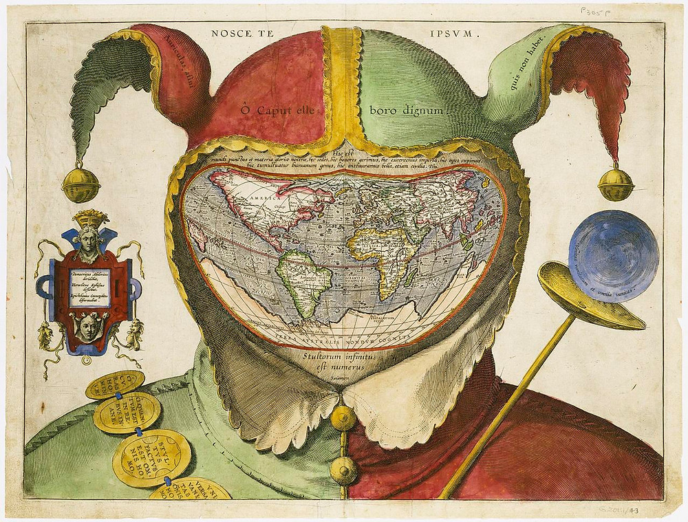 A map of the world is contained within a fool's cap. To the right is a narrow golden scepter, on the left a series of amulets are draped over the fool's shoulder. Text translated in the caption is strewn about the image.