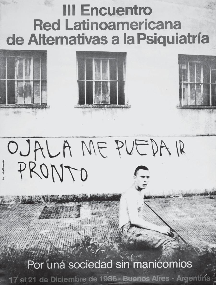 "A man sits on the ground in front of a wall where ""I hope I can leave soon"" is written in Spanish."