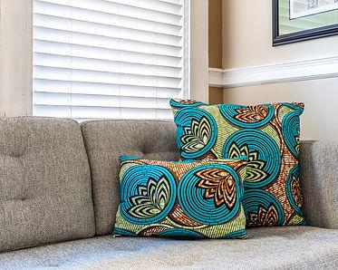 Lotus flower African print decorative pillows on gray sofa