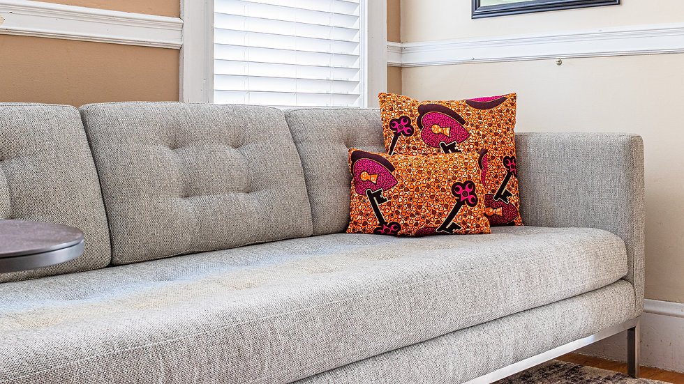 African print decorative pillows with heart and key design in orange, brown, and purple on gray living room sofa