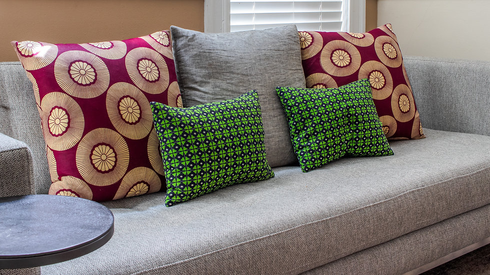 Burgundy and green African print ankara pillow arrangement on gray sofa