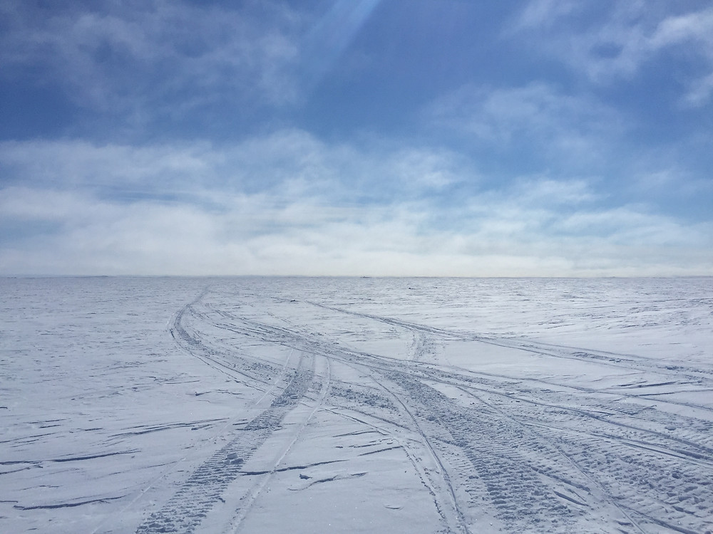 An Arctic landscape photos with a flat, snowy landscape with skidoo tracks visible towards. It is a sunny day with only a few whispy clouds.