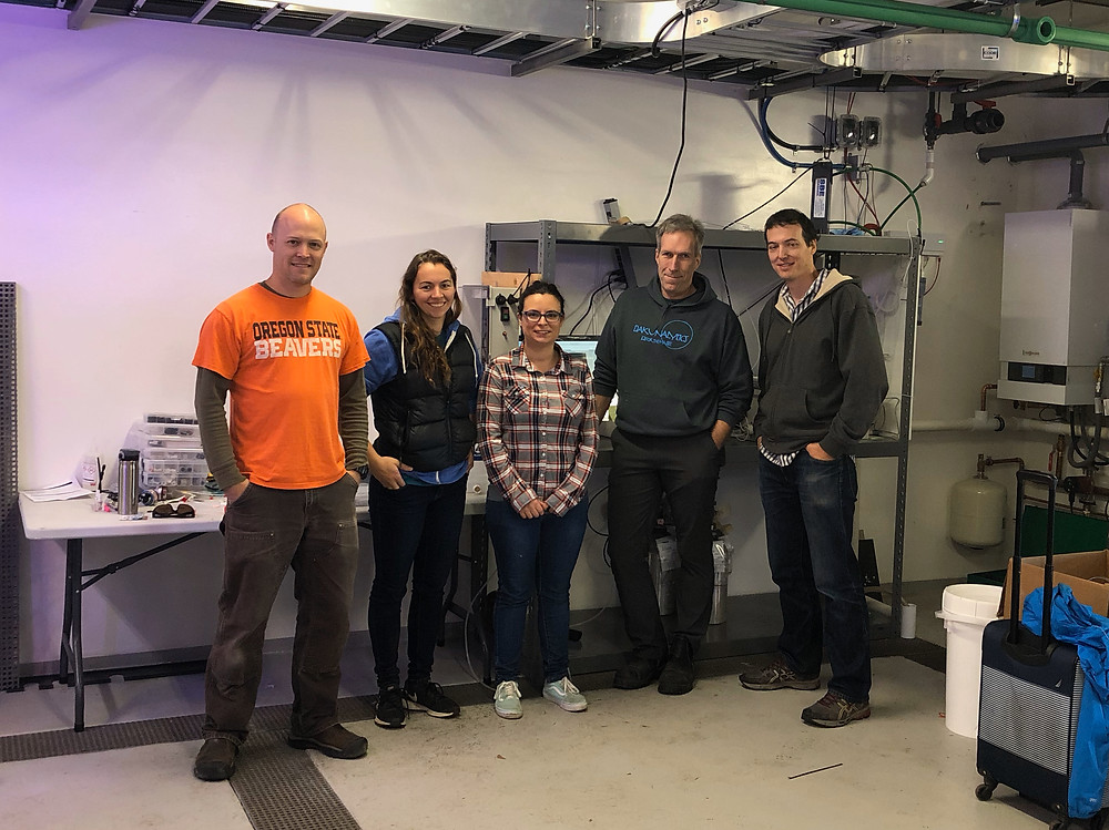 Five people standing in front of a machine used to measure water chemistry (Burkelator). From left to right: a man in an orange shirt, a woman in a puff vest, a woman with glasses and a plaid shirt, a man in a blue hoodie, a man with a green sweater
