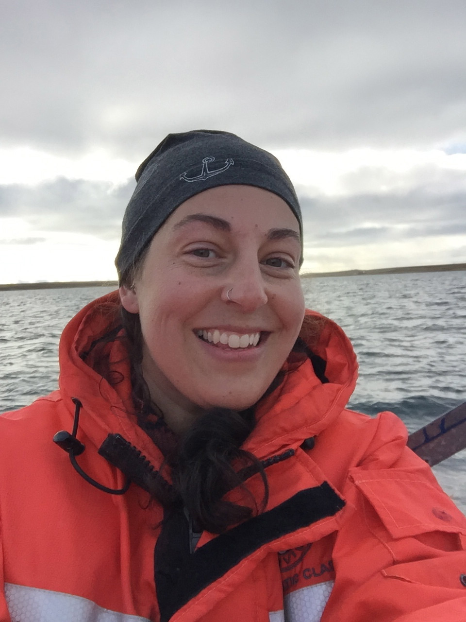 A woman wearing a grey toque and Arctic boat jacket smiles at the camera. She is on a boat with water in the background.