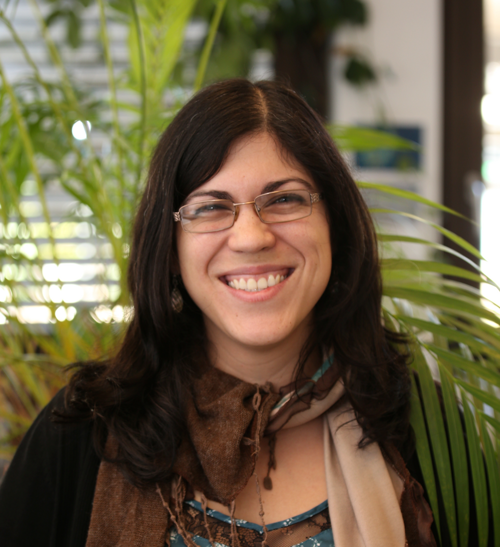A woman with brown hair and glasses smiles at the camera