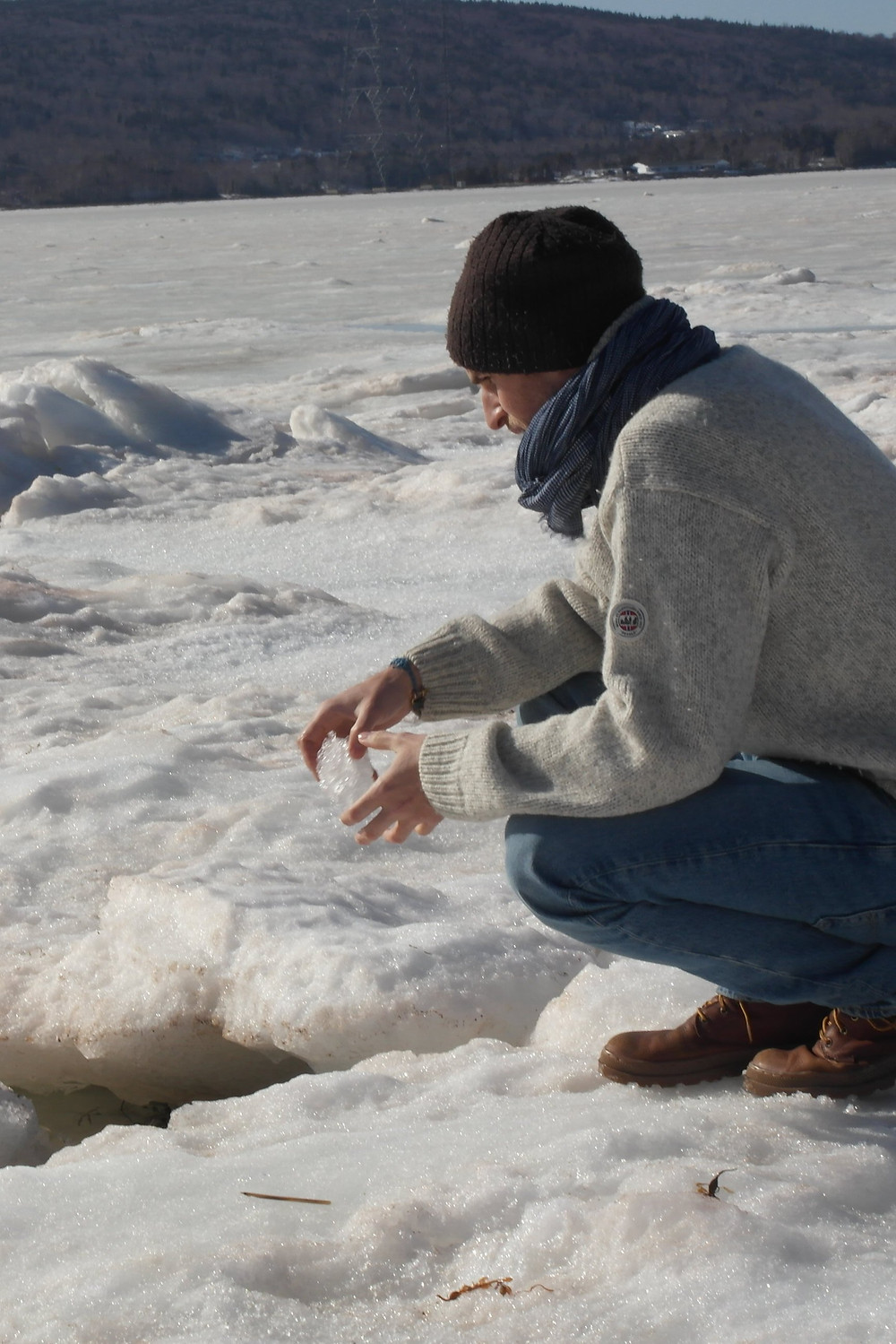 A person kneeling on ice holding a piece of ice in their hands