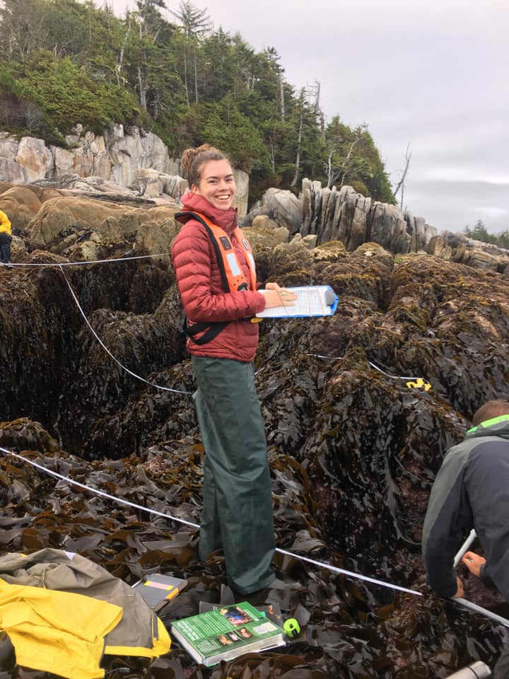 A woman wearing a red jacket and life vest smiles at the camera while holding a clipboard. She is standing in the rocky intertidal. Another person is crouched on the ground with their back to the camera as they lay down a transect line in the intertidal.
