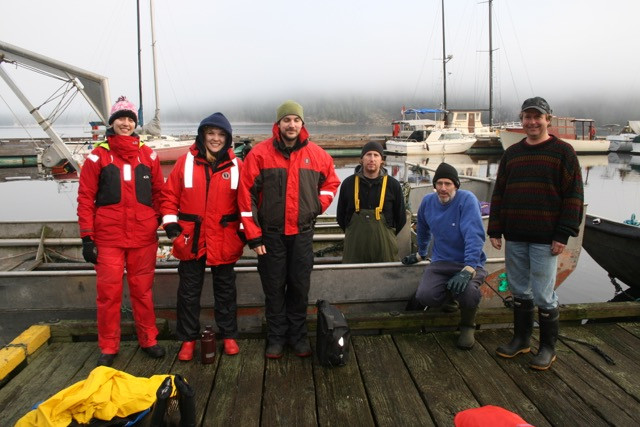 Six people in winter gear stand on a dock with a boat behind them. A man third from the right stands in the boat.