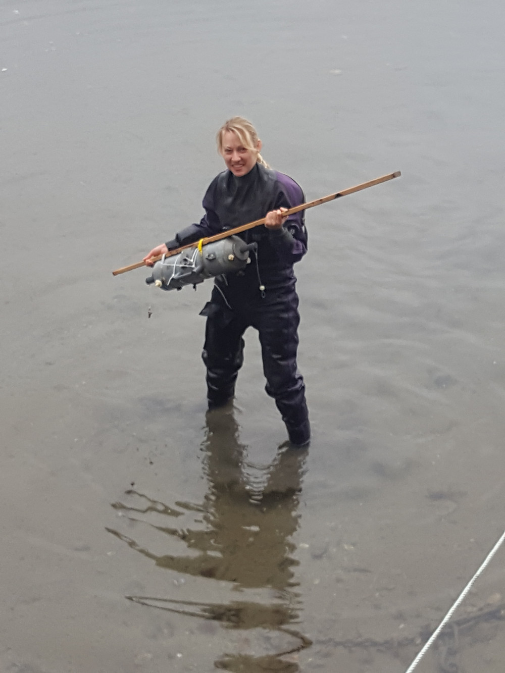 A woman wading into the water with a Niskin bottle used to collect water for sampling.