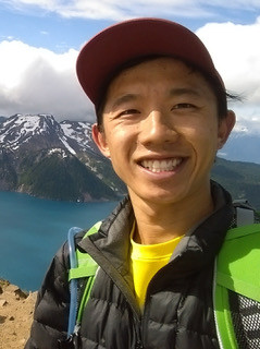 A man with a red baseball cap smiles at the camera. A lake and mountain range is visible in the background.