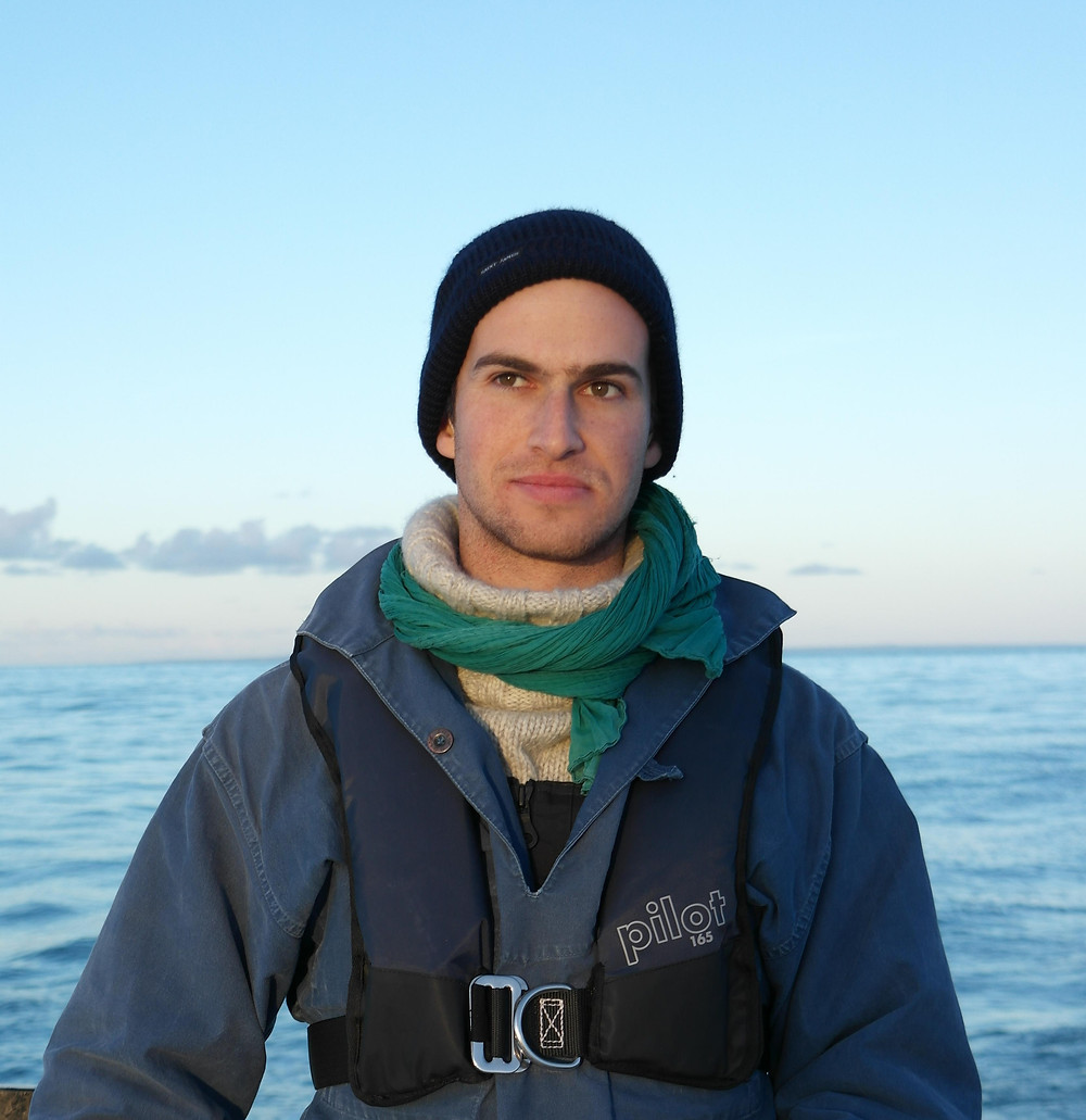 A person wearing sailing gear looks at the camera. Water is visible in the background