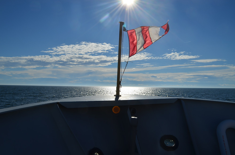 A red and white striped flag at the bow of a ship overlooking water (St. Lawrence Estuary). It is a sunny day.
