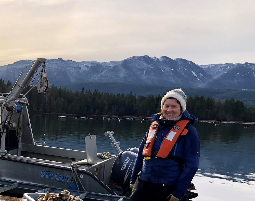 A woman wearing a toque, winter gear, and life jacket stands in front of a research boat with mountains in the background. Dr. Clara Mackenzie conducting research in Baynes Sound, British Columbia.
