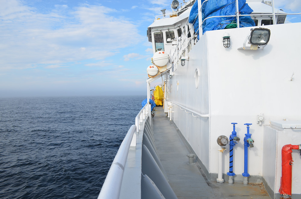 View looking down the side length of a ship out on the water (facing to the stern).