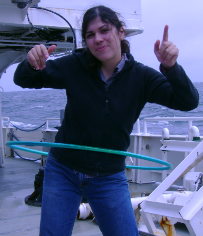 a woman standing on a ship deck actively spinning a hula hoop around her waist