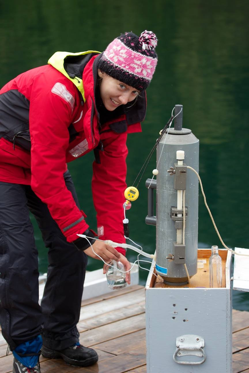 A woman in a red jacket wearing a toque taking discrete samples from a Niskin, at Evening Cove Oysters' lease.