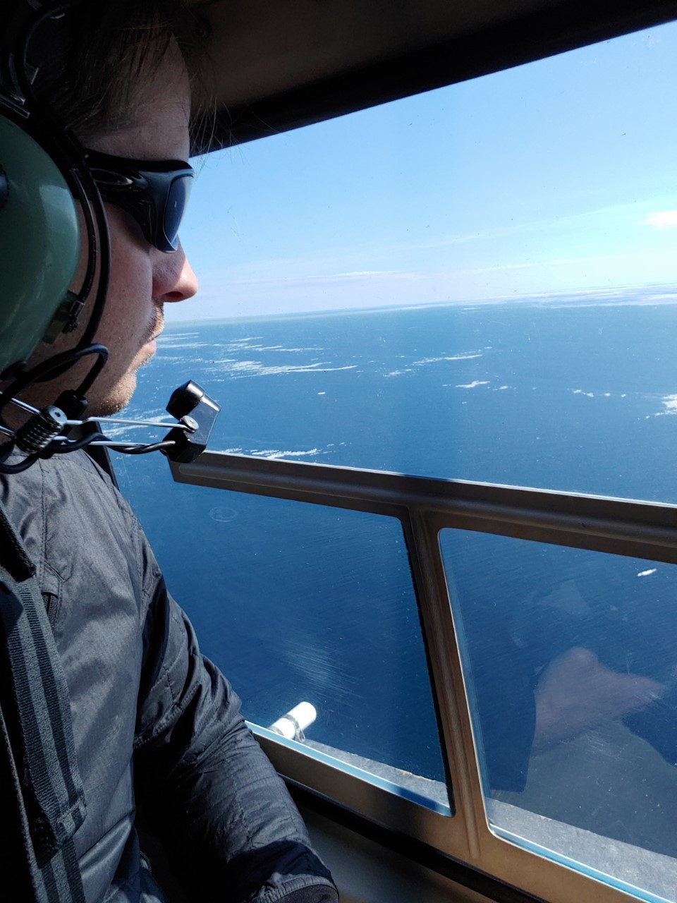 A man with sunglasses looks out a helicopter window. The view is of an ocean with some sea ice.