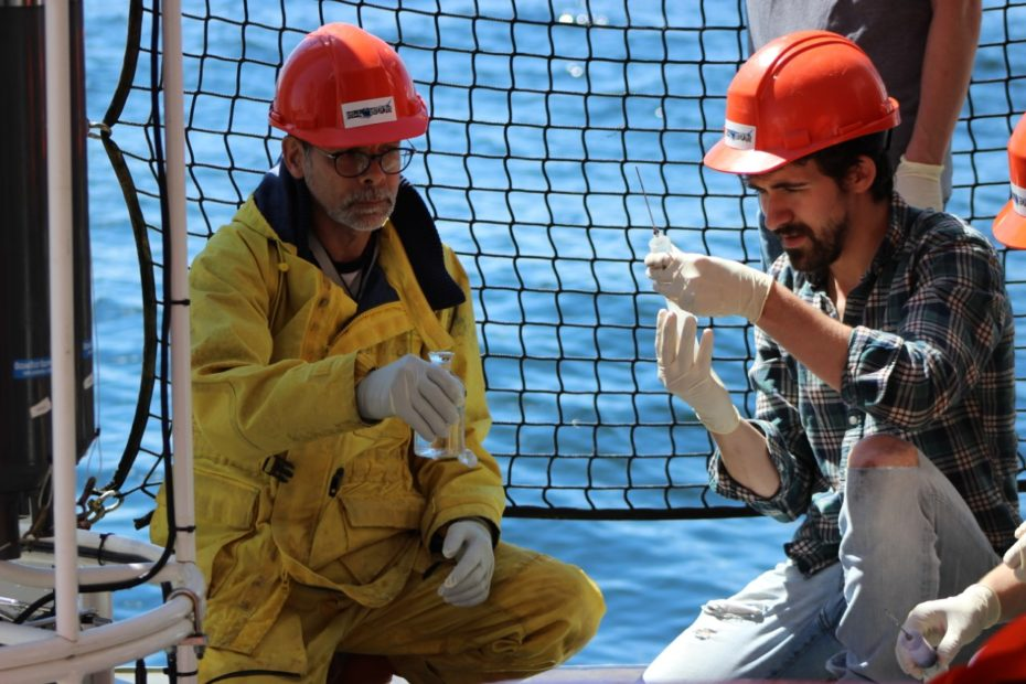 Two men in red hardhats kneel on the deck of a ship holding sampling tubes