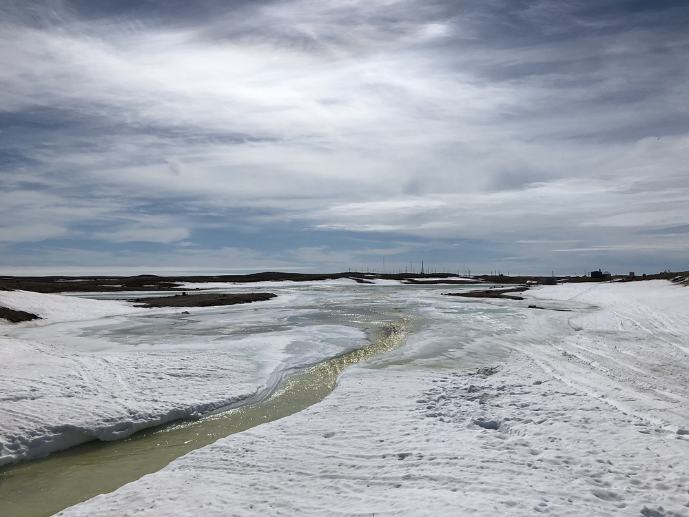 A creek meltwater channel is visible cutting through an icy riverbed and into a bay visible in the distance. The landscape is otherwise snowy and it is a sunny day.