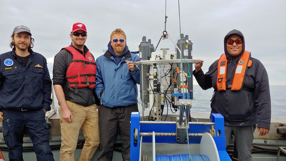 Four men stand on a boat next to a CTD/Rosette on a winch.