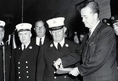 Fire Commissioner Edward Cavanaugh cuts ribbon at opening ceremony of the Fire Museum at 100 Duane Street in 1959. To his left are Chief of Department Edward Connors and Chief in Charge of Personnel Arthur Massett.