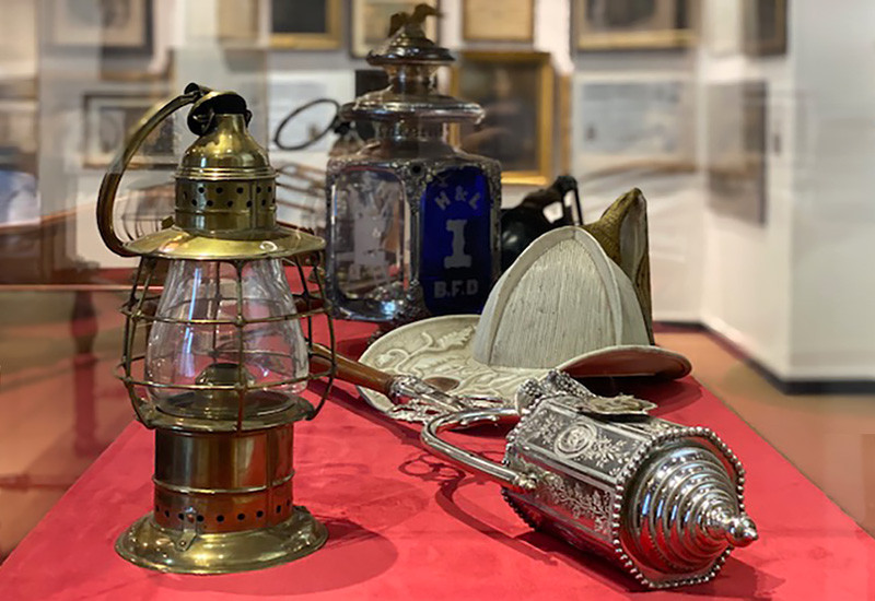 This case features typical lighting used by firefighters during the volunteer period, including a hand lantern, an ornamented apparatus lamp, and a hand carried parade torch.