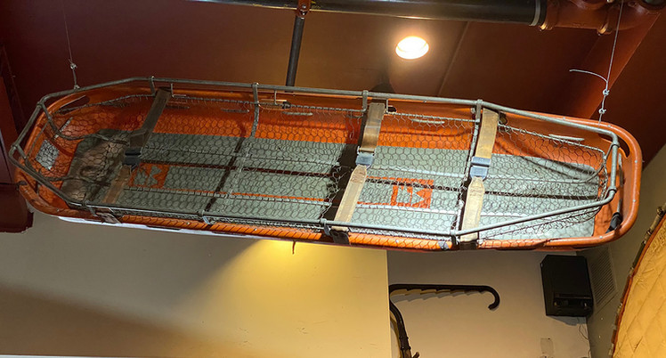 A basket type stretcher with backboard support used in rescue operations.