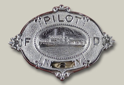 This badge depicts the New Yorker and was worn on the fireboat Pilot's cap. The New Yorker was featured on this style badge until about 1938, when the image was changed to that of the Fire Fighter.
