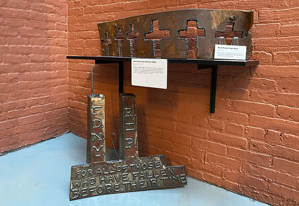 The World Trade Center memorial piece on the left was a gift to the FDNY by the Iron Workers of Local 40. The piece of steel on the right was used to make crosses for the loved ones of victims of the WTC attacks. Both are composed of steel from the WTC buildings found during during recovery operations.