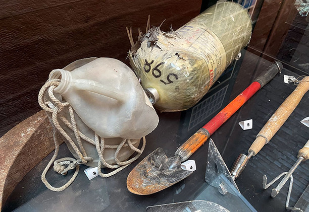 Tools and equipment recovered from the World Trade Center site. This case contains a ruptured air tank from an FDNY self-contained breathing apparatus (SCBA).