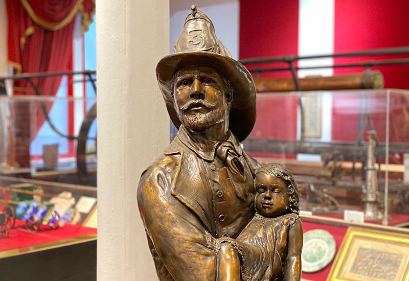Presented to New York Firefighters by the Sons of Italy Lodge 2702, this statue depicts an iconic image of the volunteer period – a fireman holding a rescued child – seen on certificates and art from the era characterizing the heroism displayed by firemen.
