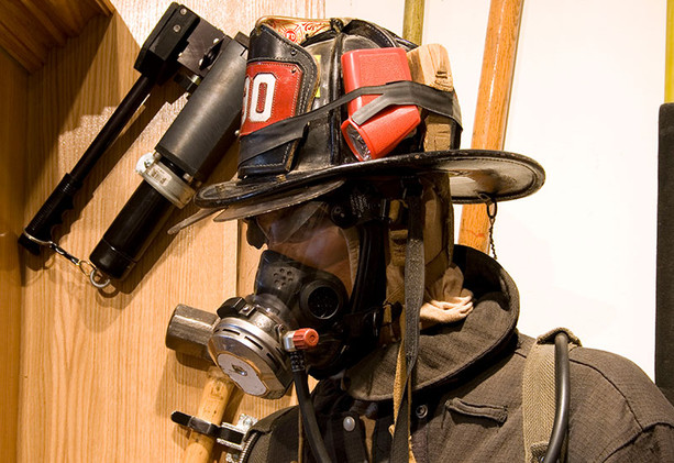 The helmet worn by this firefighter is a Cairns N5A New Yorker and has a wooden chock and disposable flashlight strapped around the outside. The firefighter is also wearing a Scott Air-Pak, a type of self-contained breathing apparatus.
