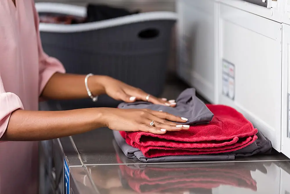 Close-up-of-young-woman-folding-clothes-