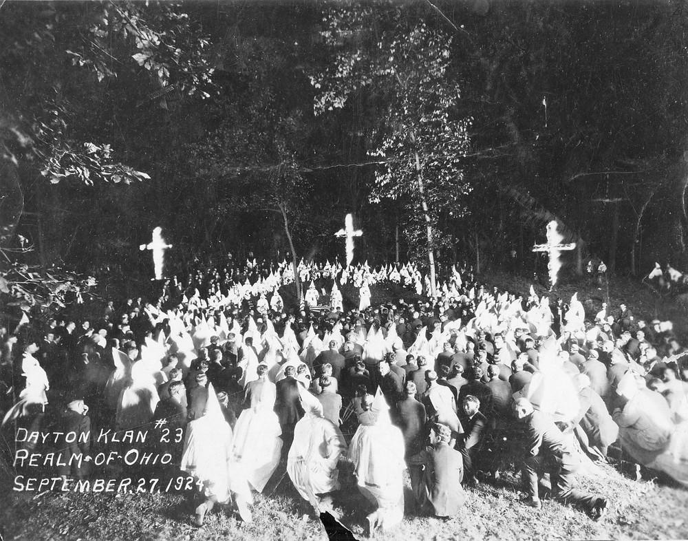 Kneeling before burning crosses, KKK rally in Dayton, Ohio, 1924