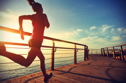 healthy lifestyle sports woman running on wooden boardwalk sunrise seaside.jpg