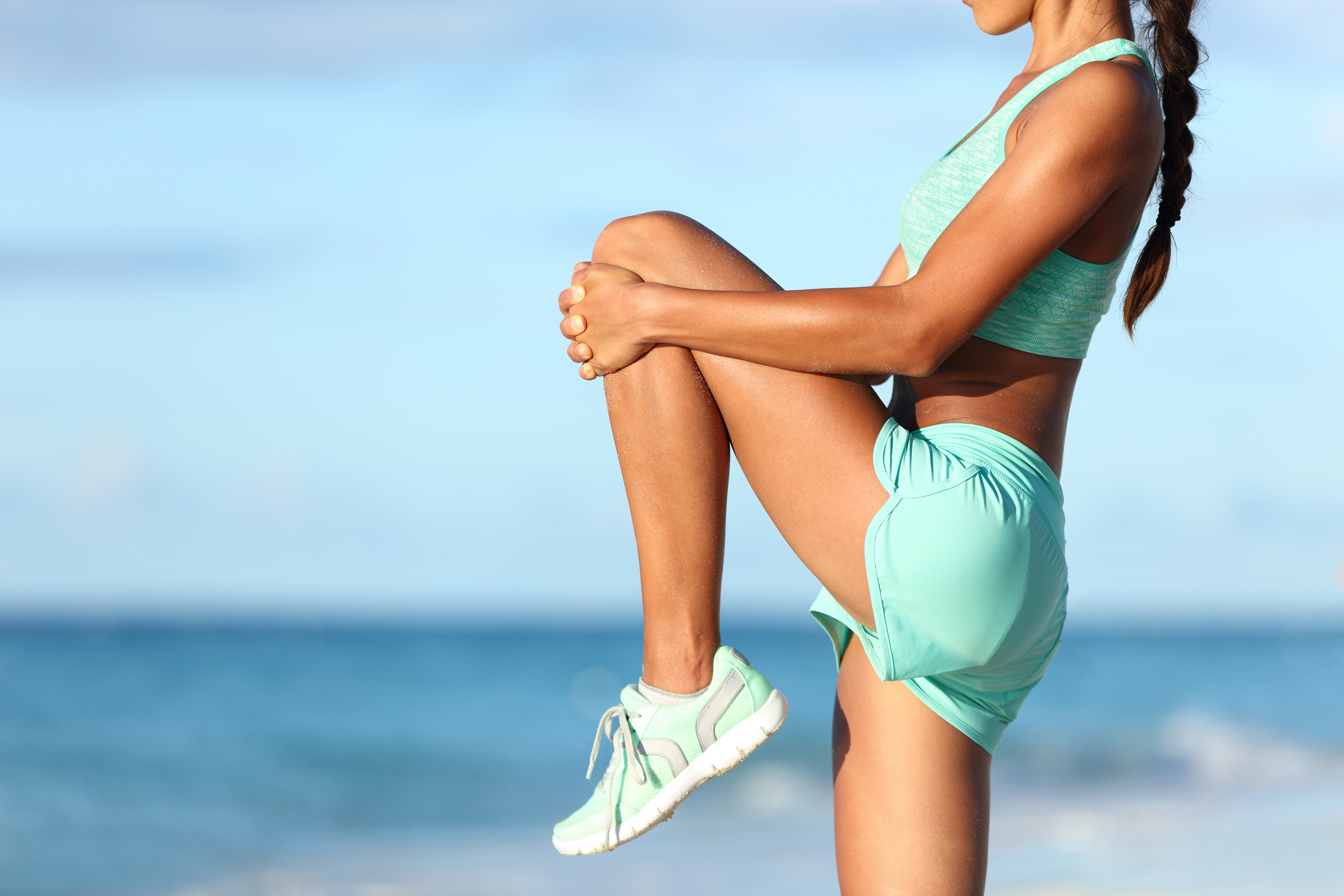 Fitness runner body closeup doing warm-up routine on beach before running, stretching leg muscles wi