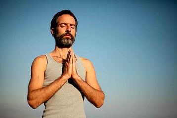 Na imagem aparece um homem com as mãos unidas a frente do peito, como em sinal e oração e/ou agradecimento.