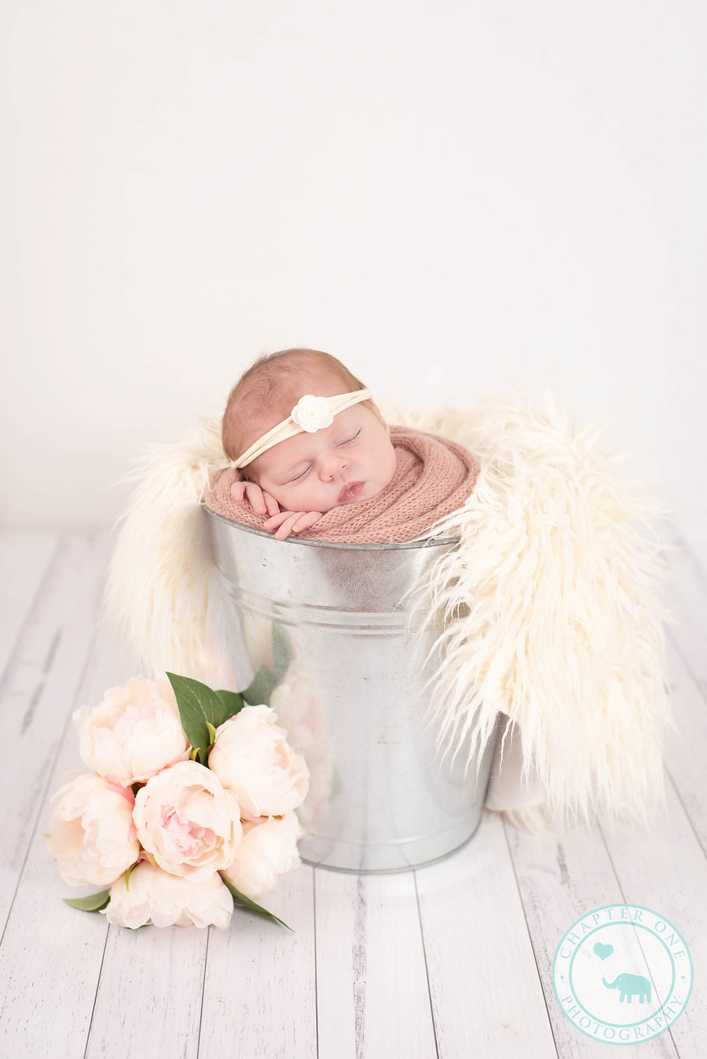 Newborn Girl in a bucket with flowers