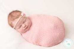 newborn girl in pink wrap