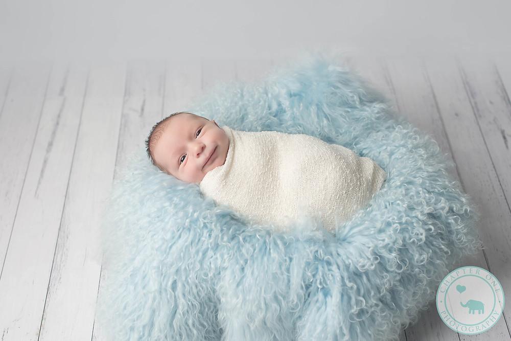 Smiling newborn boy on blue fur