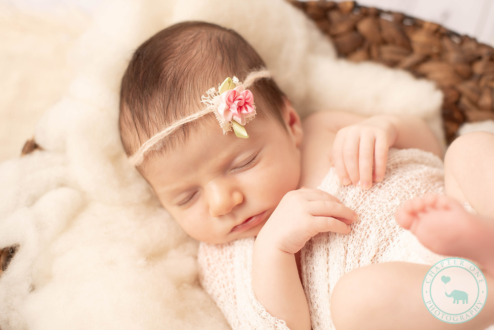 Newborn girl asleep in basket with pink headband