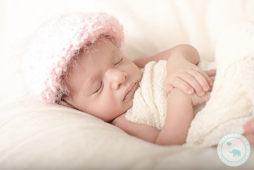 Newborn girl in pink fluffy hat