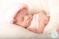 Newborn girl in pink fluffy hat