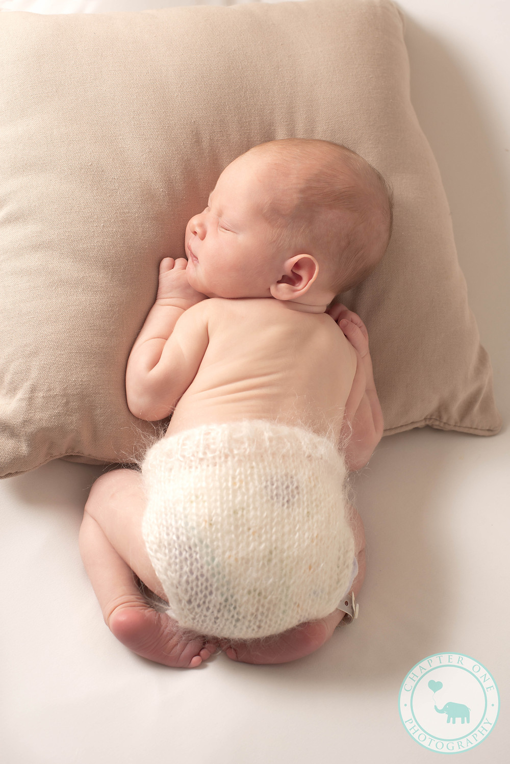 Newborn boy asleep on pillow