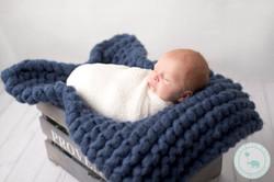 Newborn boy in crate with blue