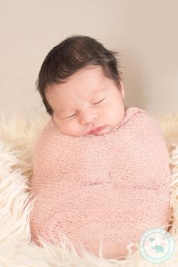 Newborn girl in sac pose wrapped
