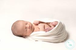 Baby boy in egg pose white wrap