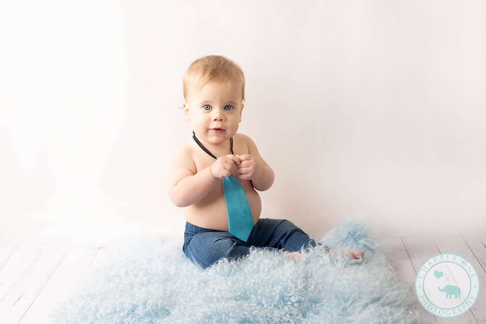 Milestone session for 1 year old boy on blue fur with tie