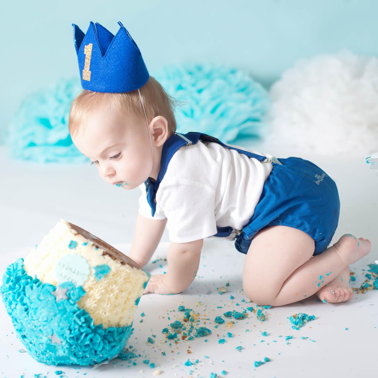 baby pushes cake onto floor
