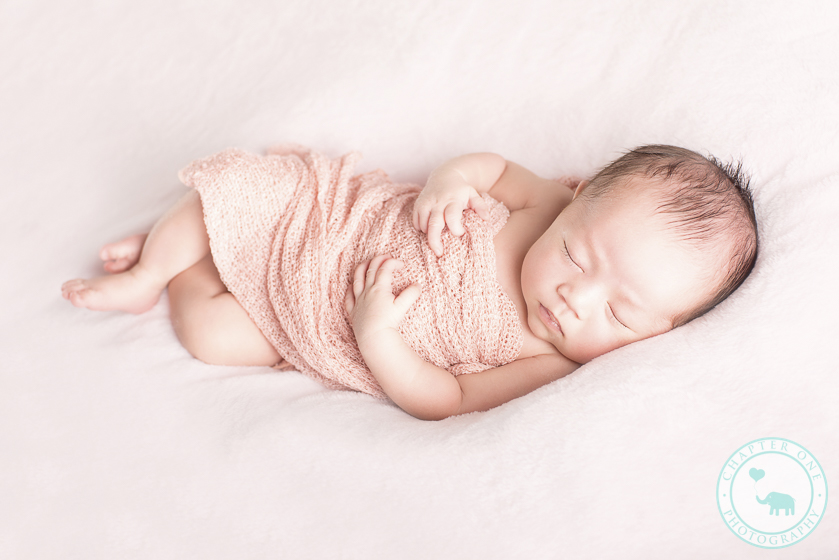 Newborn girl asleep on pink blanket